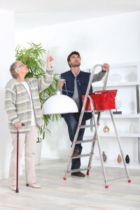 Senior Woman with a Cane directing younger man on a ladder where to hang a ceiling lamp